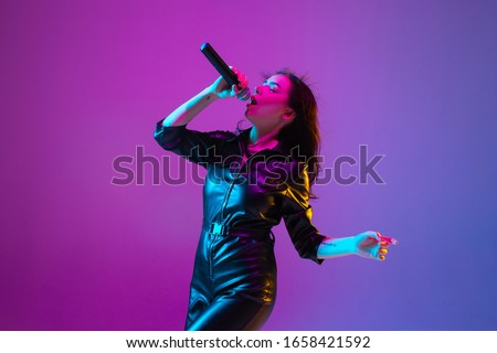 Caucasian female singer portrait isolated on purple studio background in neon light. Beautiful female model in black wear with microphone. Concept of human emotions, facial expression, ad, music, art. #1658421592