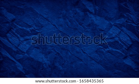Blue grunge background. Toned mountain texture. Close-up. Navy blue rocky texture with copy space for your design. Colored rock background.