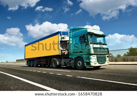 Yellow truck is on highway - business, commercial, cargo transportation concept, clear and blank space on the side view #1658470828