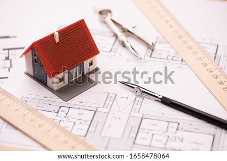 A model house on blueprints with keys to the new home Close up Royalty-Free Stock Photo #1658478064
