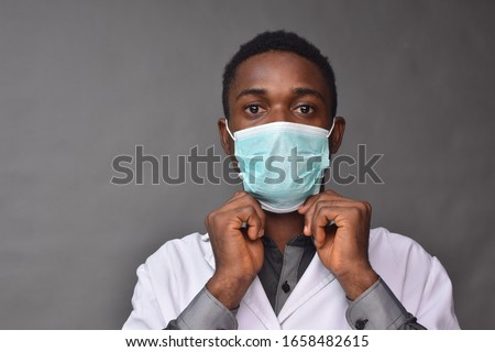 young black man wearing a white coat and face mask #1658482615