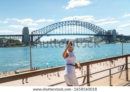 Woman taking selfie with mobile phone at iconic Sydney Harbor Bridge. Cityscape, water, with buildings in CBD area. Tourist attraction in Australia. Technology, tourism, travel, taking a photo concept