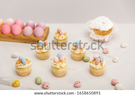 Cupcakes with painted chicken and quail eggs near traditional easter cake isolated on grey background #1658650891