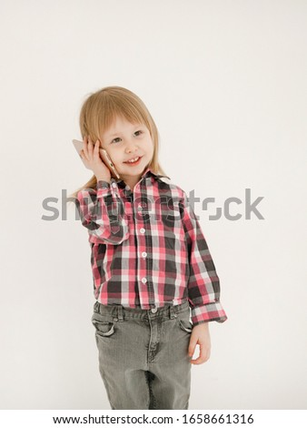 Emotional portrait of a cheerful and cheerful beautiful little girl looking with a smile in the mirror while using a smartphone with her grandmother, isolated on white background.Happy childhood #1658661316