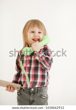 Emotional portrait of a cheerful and cheerful beautiful little girl looking with a smile out the window while talking on a telephone receiver connected to a smartphone, isolated on white background #1658662912