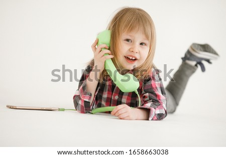 Emotional portrait of a cheerful and cheerful beautiful little girl looking with a smile out the window while talking on a telephone receiver connected to a smartphone, isolated on white background #1658663038