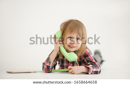 Emotional portrait of a cheerful and cheerful beautiful little girl looking with a smile out the window while talking on a telephone receiver connected to a smartphone, isolated on white background #1658664658
