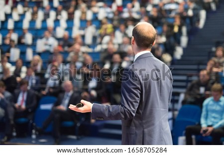 Rear view of speaker giving a talk on corporate business conference. Unrecognizable people in audience at conference hall. Business and Entrepreneurship event. #1658705284