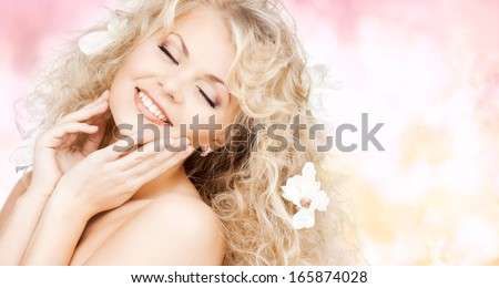 health and beauty concept - happy woman with closed eyes and flowers in hair #165874028