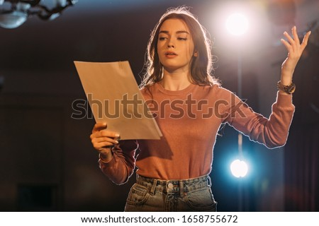 young actress reading scenario on stage in theatre Royalty-Free Stock Photo #1658755672