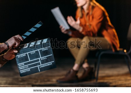 selective focus of actor with clapboard in front Royalty-Free Stock Photo #1658755693