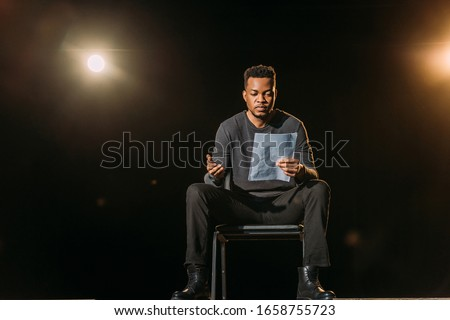 handsome african american actor holding scenario on stage during rehearse Royalty-Free Stock Photo #1658755723