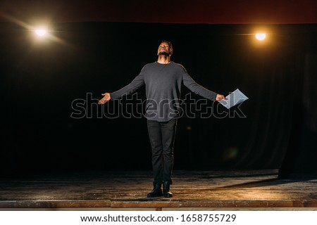 african american actor holding scenario and standing on stage during rehearse Royalty-Free Stock Photo #1658755729