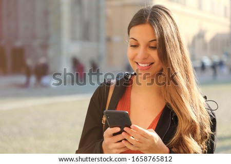 Happy beautiful high school girl smiling and texting with smart phone outdoors on sunset in spring day