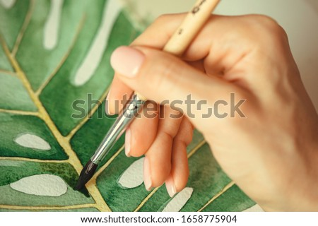 A woman paints a palm leaf with watercolor paints. Watercolor drawing of a tropical leaf. Female hand holds a watercolor brush. Watercolor drawing. Elegant female hand. #1658775904