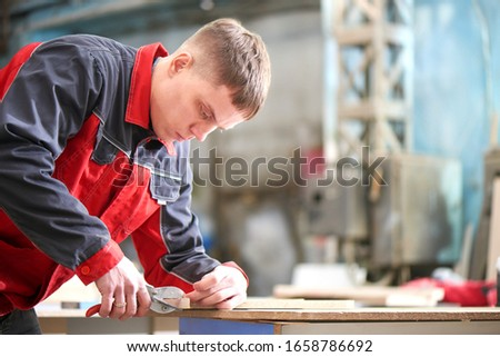 Process of production and manufacture of wooden furniture in furniture factory. Worker carpenter man in overalls processes wood on special equipment #1658786692