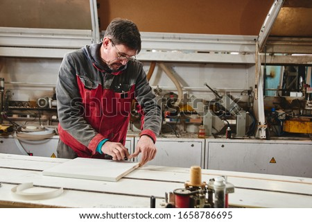 Process of production and manufacture of wooden furniture in furniture factory. Worker carpenter man in overalls processes wood on special equipment #1658786695