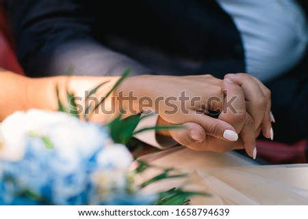 the groom gently holds the bride's hand on the wedding day #1658794639