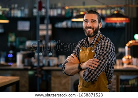 Happy satisfied bartender with apron near counter with crossed arms and looking at camera. Confident coffee shop waiter smiling at cafeteria. Successful proud young brewer at his pub with copy space. #1658871523