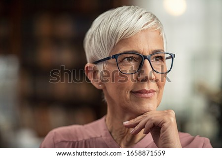 Beautiful senior business woman thinking and wearing spectacles. Thoughtful old woman teacher looking away with eyeglasses. Closeup face of mature pensive lady contemplating the future with copy space #1658871559