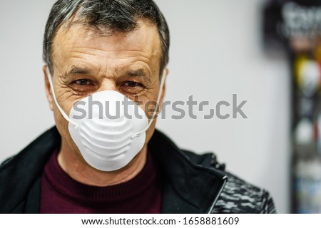 Close up portrait of senior caucasian man wearing face protective mask to protect from virus against flu anti bacteria protection health issues epidemic front view #1658881609