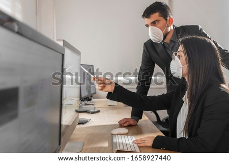 Coronavirus Office workers with mask for corona virus. Business workers wear masks to protect and take care of their health. Office working with computer. Working from home.  Royalty-Free Stock Photo #1658927440
