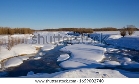 A small northern stream snow breaking after cold months. A water stream under the melting snow. Season: Winter 2020. Location: Western Siberia.  #1659002740
