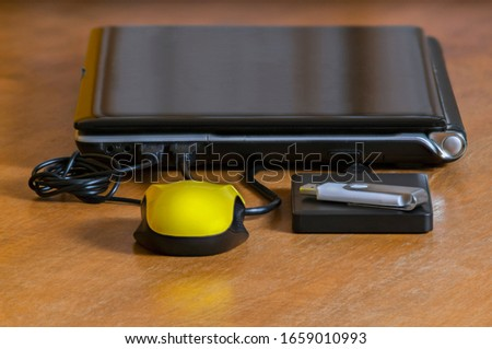 Notebook on wooden table with a mouse, an external hard drive and a pen drive #1659010993