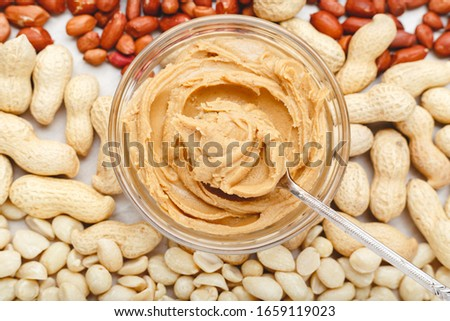 Creamy peanut paste, peanut butter in open glass jar in the center of peanuts food background. Peanuts in shell, peeled peanuts on white background . Vegan food concept. Creamy peanut paste flat lay. #1659119023