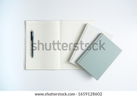 Books and open notebooks on a white desk #1659128602