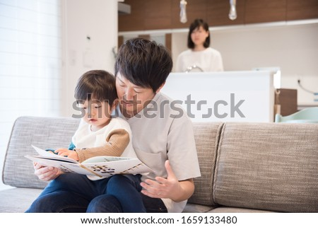Father reading a book in the living room