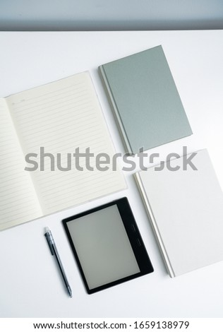 ebook and books on white desktop.Books and open notebooks on white background. #1659138979