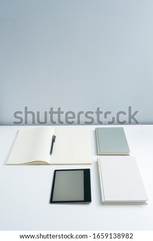 ebook and books on white desktop.Books and open notebooks on white background. #1659138982