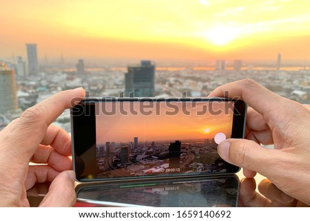 Young people take pictures of the buildings in the city. Sunrise time He uses a high-angle recording photo phone.Travel concepts and technology #1659140692