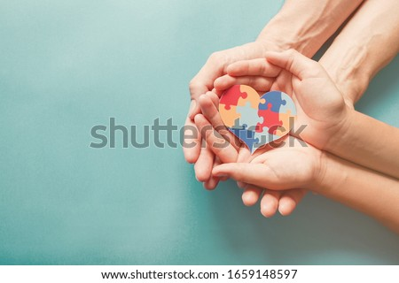 Adult and chiild hands holding jigsaw puzzle heart shape, Autism awareness, Autism spectrum disorder family support concept, World Autism Awareness Day #1659148597