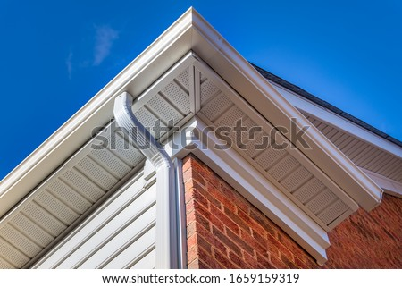 Close up of white frame gutter guard system, eaves through, fascia, drip edge, colonial white soffit with ventilation, brick facade siding on a luxury American single family home neighborhood USA #1659159319