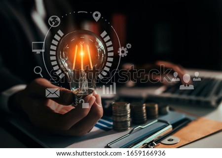 Businessmen holding light bulbs, ideas of new ideas with innovative technology and creativity. Network interface icons, Selective focus. #1659166936