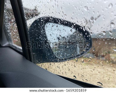 This is a picture of a side mirror with water drops.