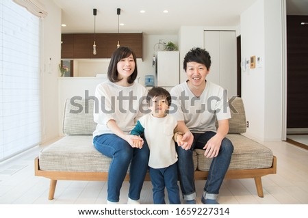 A family of three relaxing in the living room #1659227314
