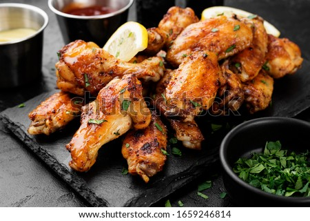 Baked chicken wings served with different sauces and lemon. Black background #1659246814