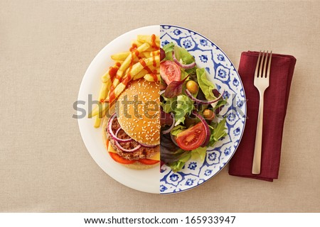 Low fat healthy salad against unhealthy greasy burger Royalty-Free Stock Photo #165933947