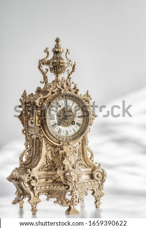 vintage bronze watch , antique clock photo, bronze fireplace clock, eight o'clock on the dial , 8 pm  on the dial of the old clock, golden old desktop clock #1659390622