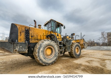 Wheel loader rides on a construction site. Special construction equipment for earthmoving and handling operations. #1659414799