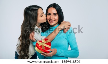 Happy mother's day. Close-up photo of a charming lady in turtleneck sweater, holding a present in a heart-shaped box, given to her by her kid, who is kissing her in a cheek.