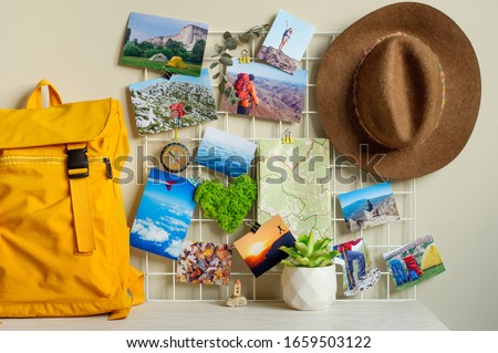 Travel hipster mood board with printed photographs, map, compass, green moss heart and hat on the wall near backpack and succulent on the table.