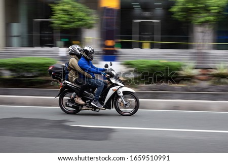 Manila, Philippines - February, 29, 2020: Motorcyclist with passenger  drives along the road in Makati #1659510991