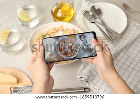 Food blogger taking picture of tasty pasta with shrimps and tomatoes at light table, closeup