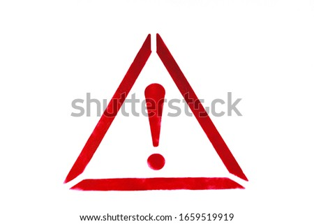 Exclamation mark in triangle drawn by red paint on white wall. Warning sign to prevent potential problems traffic accident. Close-up.