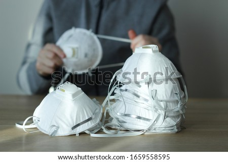Coronavirus panic concept. Dust respirator masks on the table and a person in blurred background. N95, FFP2, COVID-19.  #1659558595