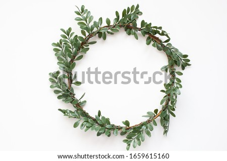 Green wreath with leaves on white background. Wreath made of branches. Flat lay, top view, copy space. Spring composition. Flowers composition. Easter. Boxwood wreath for Christmas. Scandinavian style #1659615160